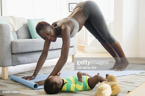 black mother practicing yoga with baby boy in living room