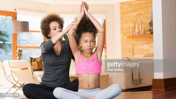 Black mother sitting on floor teaching yoga to daughter