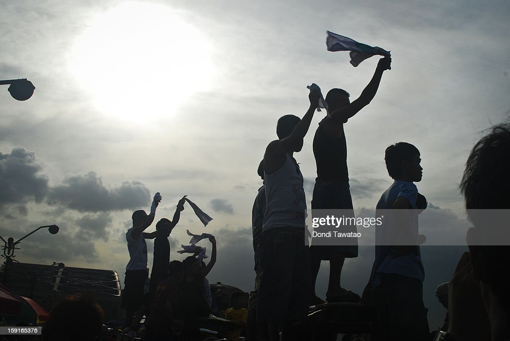 Black Nazarene devotees cheer from rooftops during the 406th feast of The Black Nazarene on January 9, 2013 in Manila, Philippines. Devotees march barefoot as a sign of sacrifice during the procession as the Black Nazarene is carried in turn through Manila's thouroughfares. The dark wood sculpture of Jesus was brought to the Philippines in the 1600s by Spanish missionaries from Mexico to the Philippines and is revered by Catholic devotees who claim the statue possess miraculous powers. Security authorities monitoring the day long procession estimated the crowd at around 2 million people at its peak.
