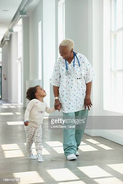 Black nurse walking in corridor with girl