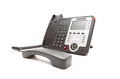 Black IP office phone isolated on white background closeup