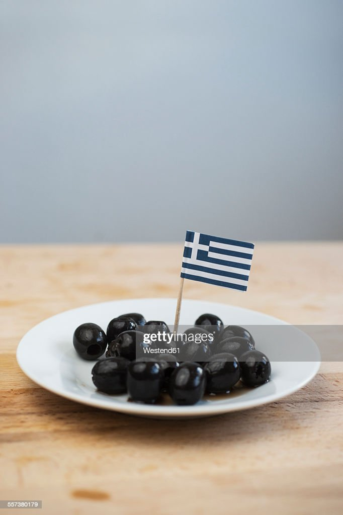 Black olives with small little greek flag on plate