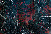 Black marble onyx texture with white cracks and red spots