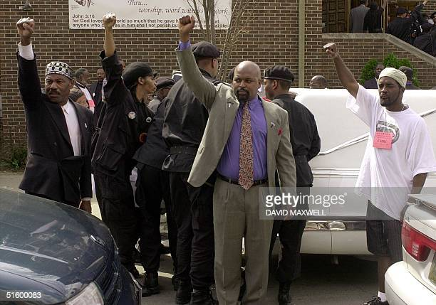 Black Panther members serving as pall bearers give the black power salute as they load the casket of Timothy Thomas into a hearse following the...