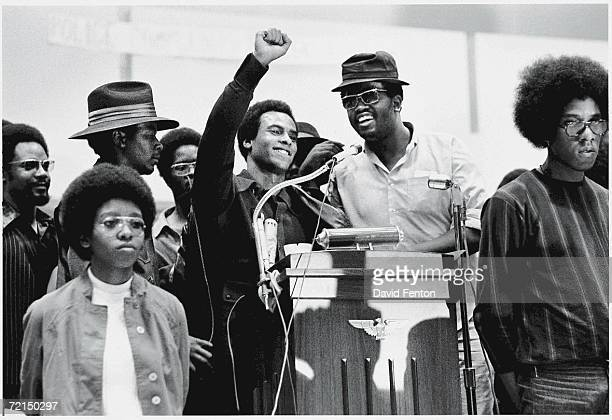 Black Panther Party cofounder Huey P Newton smiles as he raises his fist from a podium at the Revolutionary People's Party Constitutional Convention...