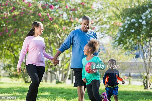 Black parents walking in park, children running, playing