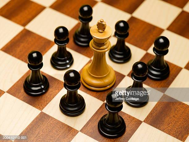 Black pawns surrounding white king on chessboard