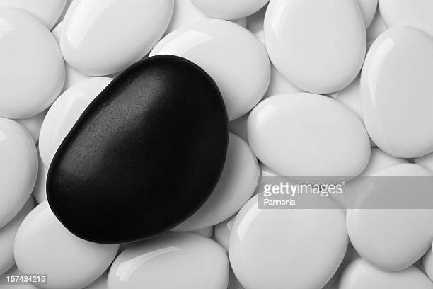 Black pebble on white pebbles