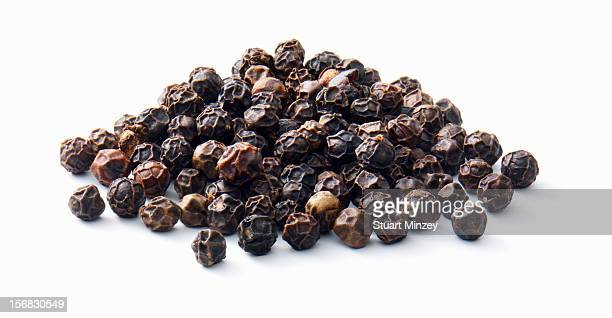 Black peppercorns on a white background