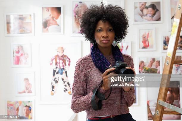 Black photographer holding camera in studio