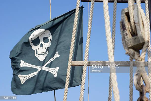 Black pirate flag , blue cloudless sky and wooden pulley