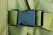 black carbine on harness on the green matter of the backpack