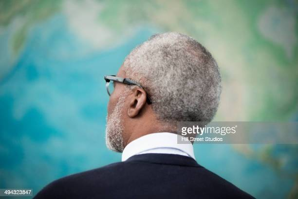 Black professor looking at map