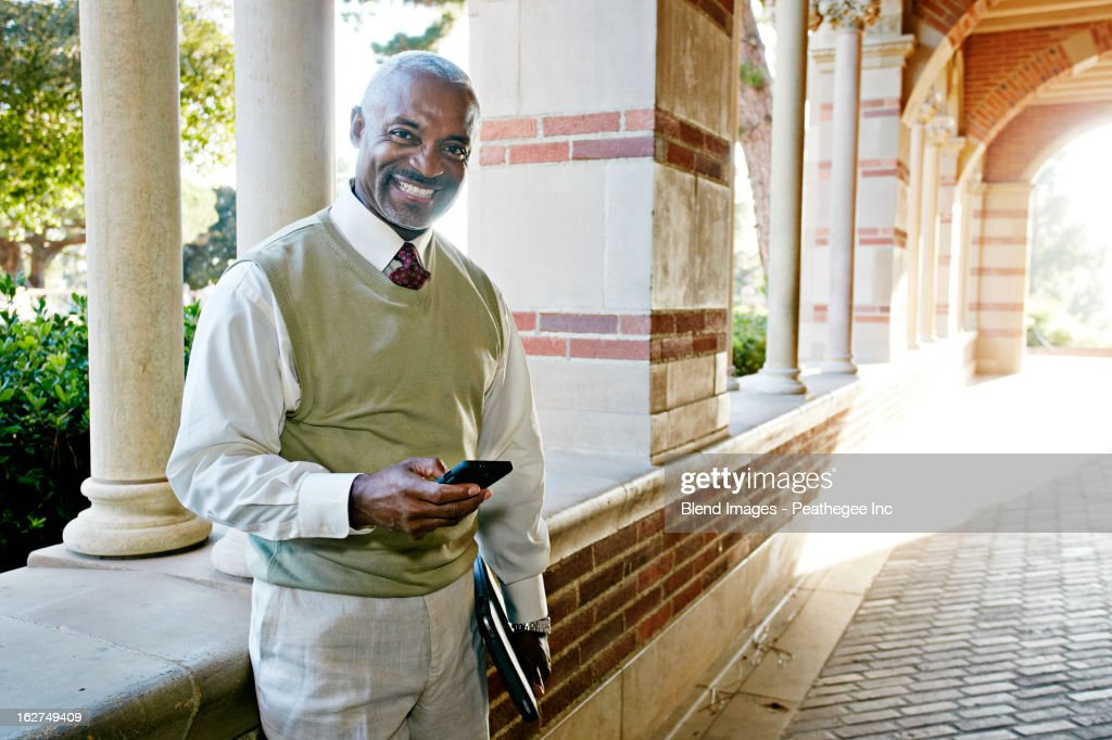 Black professor text messaging on cell phone