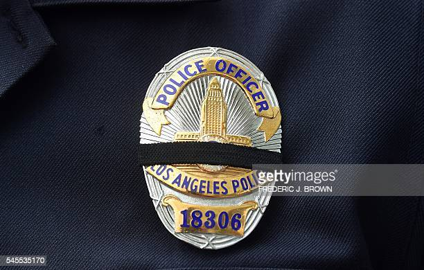 Black ribbons are seen on the badges of a Los Angeles Police officers during a graduation ceremony for new recruits on July 8 2016 in Los Angeles...