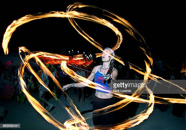 Black Rock City Nevada––A fire dancer practices her craft on the final night of Burning Man in anticipation of the burning of the 60–foot tall...