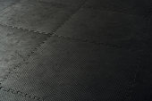 Black rubber floor mat and tiles inside a gym. Black rubber fitness floor texture and background. EPDM safety mats reduce the injury risk caused by falls on playgrounds and sport facilities.