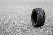 Black rubber tire rolling on the dry asphalt road in summer day. Seasonal tire change. Mock up for special offers as advertising or other ideas. Copy space. Empty place for text or logo.
