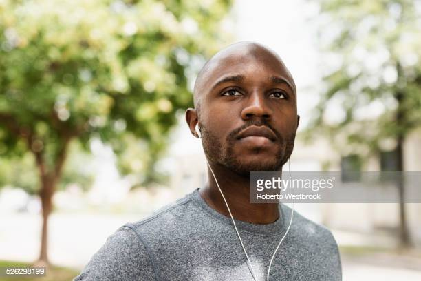 Black runner resting in park with earbuds