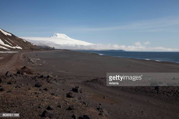 Black sand beach and snow covered Beerenberg volcano on Jan Mayen volcanic island in the Arctic Ocean in spring