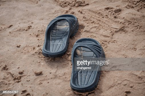Black sandals on the beach sand : Stock Photo