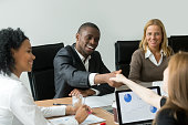 Black satisfied businessman handshaking white businesswoman concluding contract, smiling happy african entrepreneur and new female partner shaking hands at group meeting in notary office