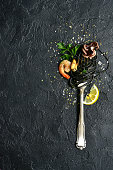 Black seafood spaghetti on fork over black slate, stone or concrete background.Top view with copy space.