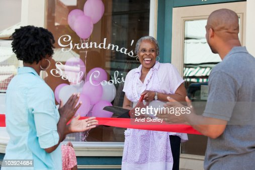 Black shopkeeper cutting ribbon at storefront