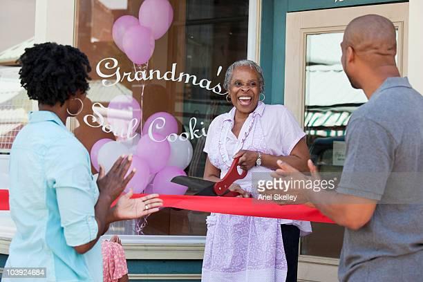 Black shopkeeper cutting ribbon at storefront