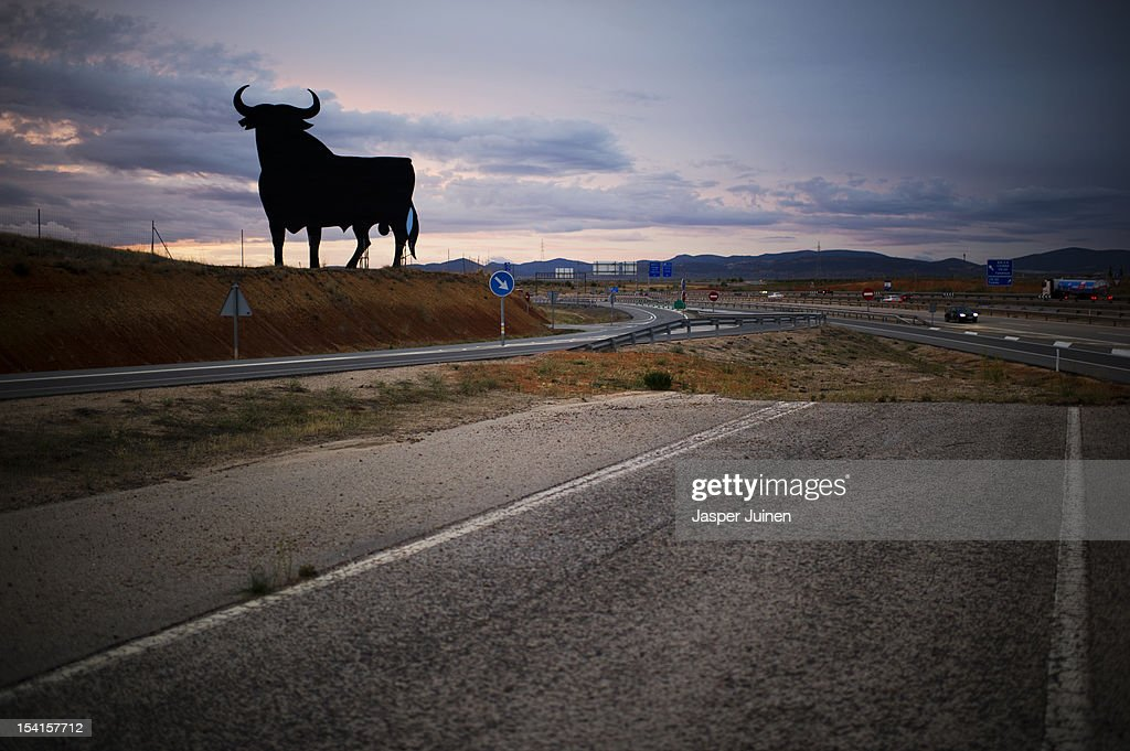 A black silhouetted image of a bull stands besides an old road and a newly constructed high way stretching through the windswept La Mancha countryside on October 12, 2012 in the direction of the small industrial town of Villacanas, Spain. During the boom years, where in its peak Spain built some 800,000 houses a year, more than Britain, Germany and France combined, and millions of wooden doors where needed, the people of Villacanas were part of a proud elite enjoying high wages and permanent jobs. Almost all of those doors used came from this small industrial town in the La Mancha province, some seven million a year, leaving with truck loads at the same time, from the now empty and silent Villacanas industrial park. With Spain in recession and the housing bubble busted, the door industry is shattered and unemployment in Villacanas, zero for nearly a generation, is rising fast.