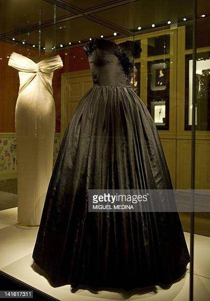 A black silk taffeta gown and a classic formal dinner dress of ivory silk crepe both worn by Diana Princess of Wales are pictured inside Kensington...