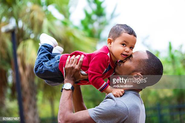 Black single dad holding two year old son in air