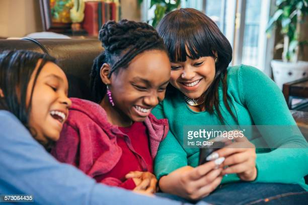 Black sisters using cell phone on sofa