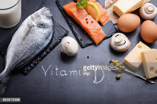 Black slate table with product rich in vitamin D and omega 3. Written word vitamin D by white chalk. : Stock Photo