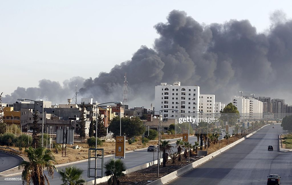 Black smoke billows across the sky after a petrol depot was set ablaze during clashes between rival militias near Tripoli's international airport on...