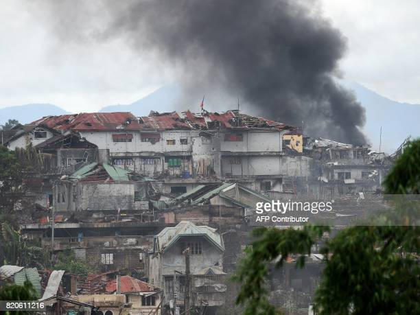 Black smoke billows from burning buildings after an aerial bombing by Philippine Air Force attack helicopters at Muslim militant positions in Marawi...