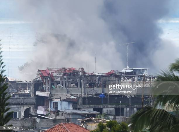TOPSHOT Black smoke billows from burning houses after an aerial bombing by the Philippine Air Force on militant Islamist positions in Marawi on the...