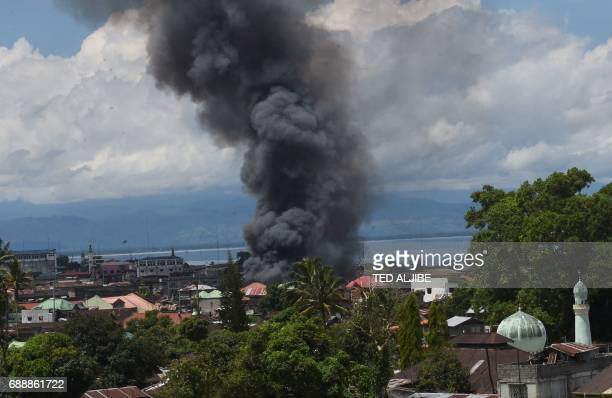 Black smoke billows from burning houses after government planes and helicopters bombed Islamic militants position in Marawi in southern island of...