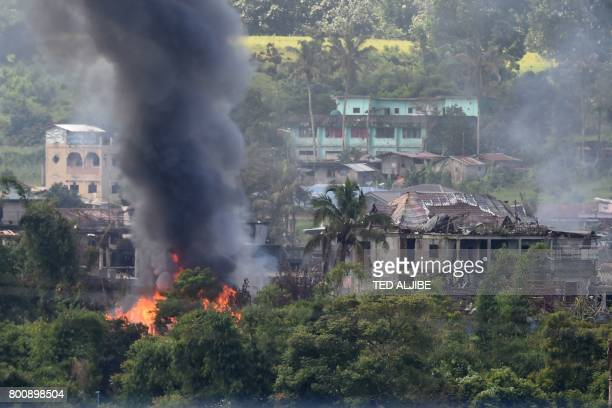 Black smoke billows from burning houses after Philippine Airforce attack planes conducted aerial bombings on Islamist militants' positions in Marawi...
