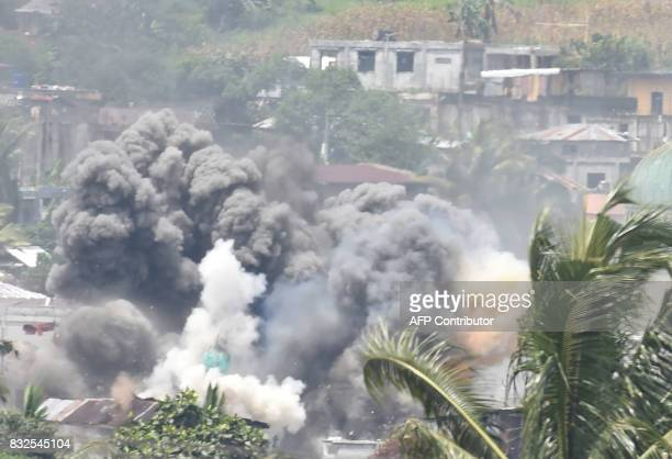 Black smoke billows from burning houses after Philippine airforce attack planes dropped bombs during the an aerial bombing at Muslim militants...