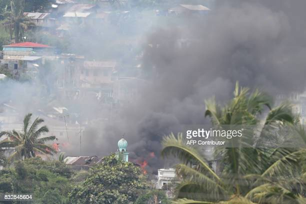 Black smoke billows from burning houses after Philippine airforce attack plane dropped bombs on Muslim militants position during an aerial bombings...