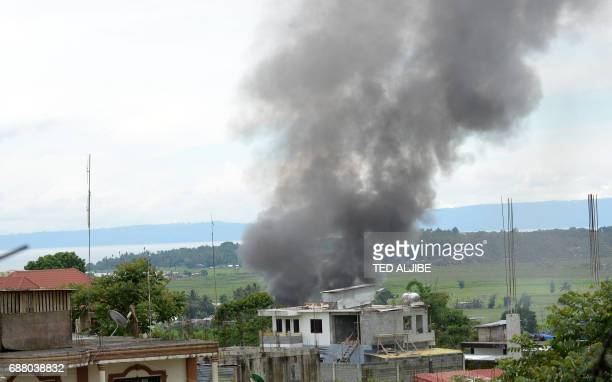 Black smoke billows from burning houses as fighting between Philippine soldiers and the ISaffiliated Maute group rages near the provincial capitol in...