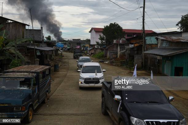 Black smoke billows from houses after military helicopters struck a position of Islamist militants as rescue vehicles speed away after rescuing...
