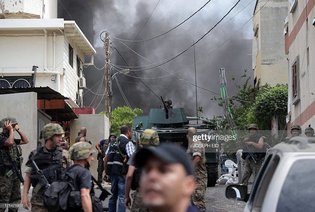Black smoke billows from the entrance of the Bilal bin Rabah mosque as Lebanese army soldiers detonate booby traps set by gunmen in the Abra district of the southern city of Sidon on June 25, 2013, after troops seized control of the headquarters of a radical Sunni sheikh whose supporters battled the army for two days, killing 16 soldiers.