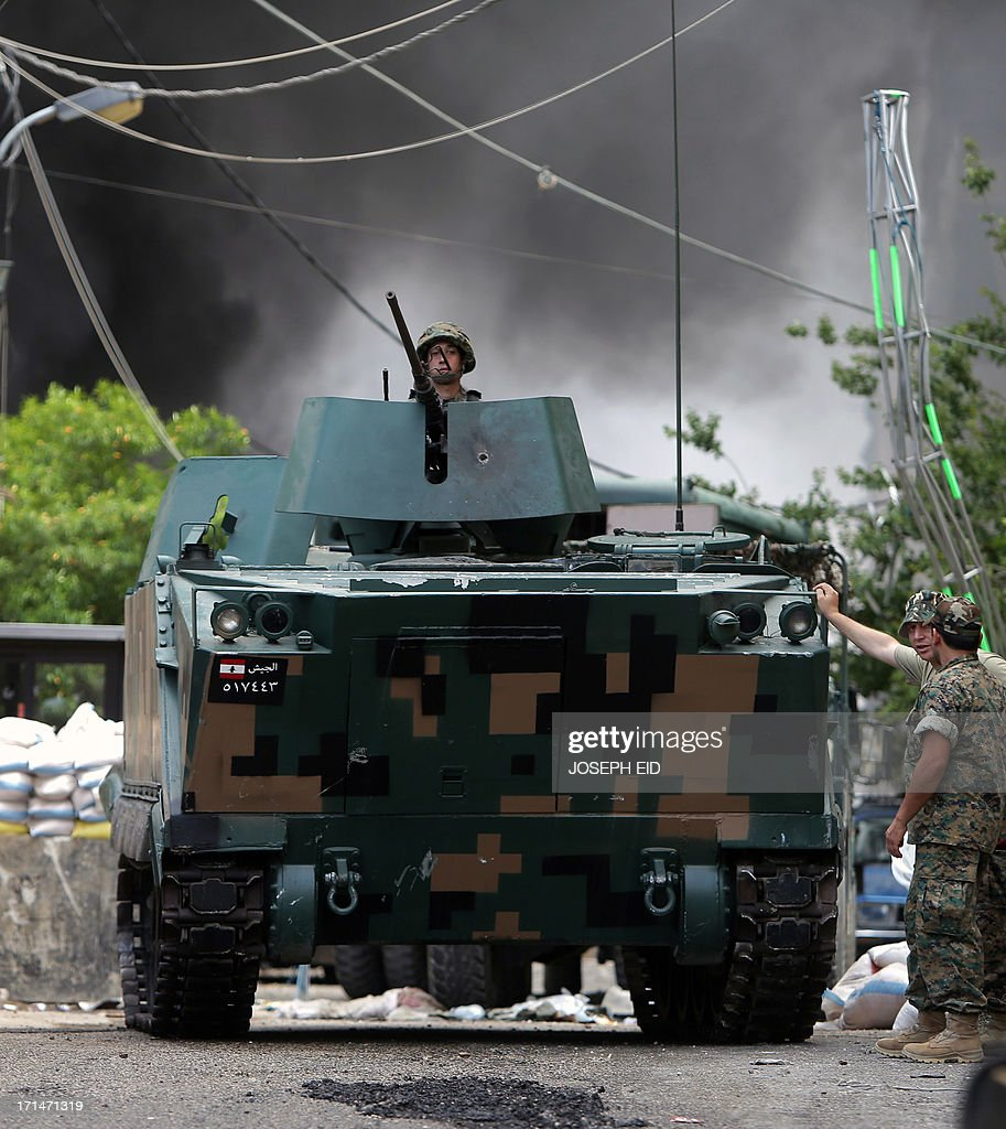 Black smoke billows from the entrance of the Bilal bin Rabah mosque behind an armored personnel carrier as Lebanese army soldiers detonate booby traps set by gunmen in the Abra district of the southern city of Sidon on June 25, 2013, after troops seized control of the headquarters of a radical Sunni sheikh whose supporters battled the army for two days, killing 16 soldiers.