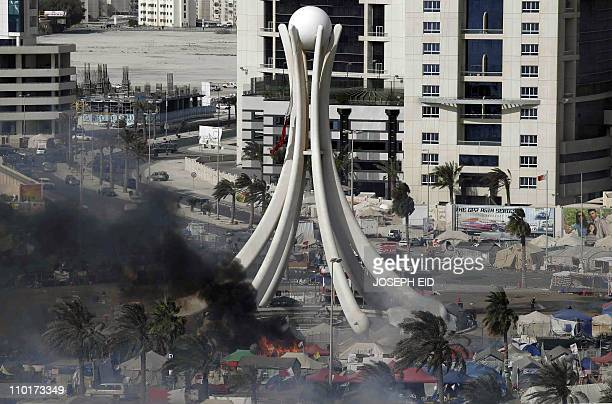 Black smoke rises from burning tents as Bahraini security troops raid the onemonthold prodemocracy sitin at Pearl Square in the capital Manama on...