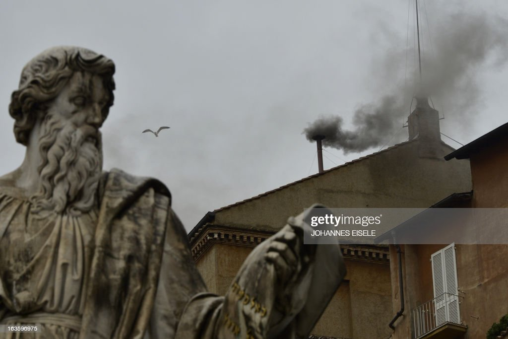 Black smoke rises from the chimney on the roof of the Sistine Chapel past St Paul's statue, meaning that cardinals failed to elect a new pope in the second ballot of their secret conclave on March 13, 2013 at the Vatican.