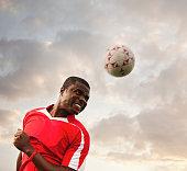Black soccer player heading the ball