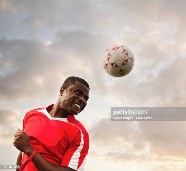 Black soccer player heading the ball