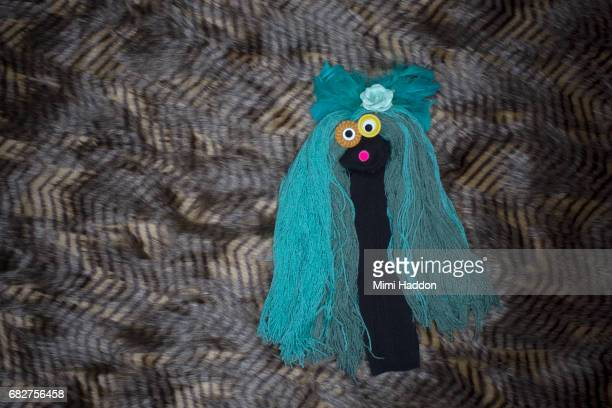 Black Sock Puppet with Blue Hair and Googly Eyes Looking at Camera
